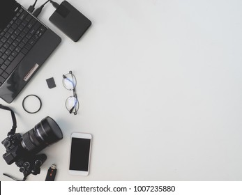 top view of photographer concept with digital camera, memory card, external harddisk and camera accessory on white background with copy space.