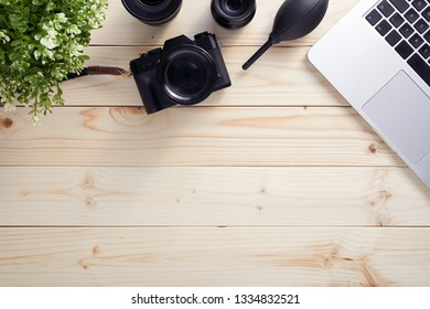 Top view of photographer desk with latptop, camera and lenses with copy space. Flat lay shot on wooden background.