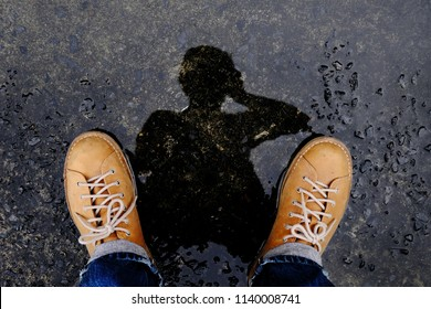 Top View of Photographer taking Self Portrait by Reflection Shadow on the Ground after stopped Raining