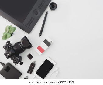 top view of photographer work station, work space concept with digital camera, book, memory card, smartphone, graphic tablet, external harddisk on white background