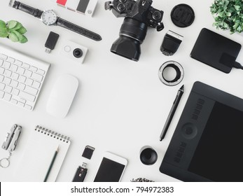 top view of photographer work station, work space concept with digital camera,pantone book, memory card, smartphone, graphic tablet, external harddisk on white background with copyspace