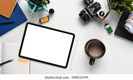Top view of photographer workplace with digital tablet, camera and accessories on white table.