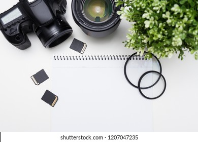 top view of photographer's workplace - camera, photography equipment and notepad over white table background