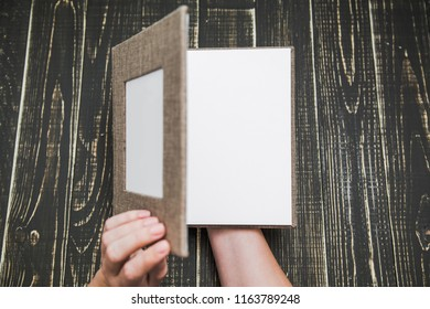 Top view photography of new brown modern photo book with empty frame for photo and plastic pages. White woman opens album with love. Isolated on wooden background. Horizontal color picture.