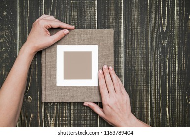 Top view photography of new brown modern photo book with empty frame for photo. White woman holds album with love. Isolated on wooden background. Horizontal color picture.