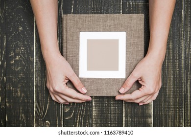 Top view photography of new brown modern photobook with empty frame for photo. White woman holds album with love. Isolated on wooden background. Horizontal color picture.