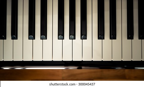 Top view of  a piano keyboard with wooden floor background in vintage looks.