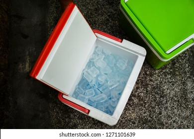 Top view of picnic cooler box with and ice cube on the ground for camping during summer vacation time. Concept of Holiday, vacations and refreshing.