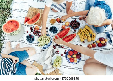Top view of a picnic tablecloth filled with plates of berries and fruits, watermelon and corn. Top view of the hands of people taking food. Fresh summer vitamin harvest. Friendly community.