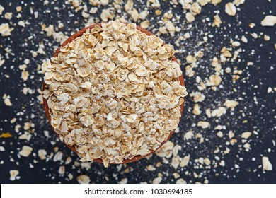 Top view picture of a bowl of oatmeal isolated on dark background, close-up.
