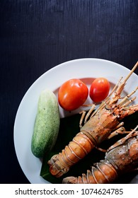 Top view picture of grilled lobster with fresh tomato and cucumber on white plate above black texture.
