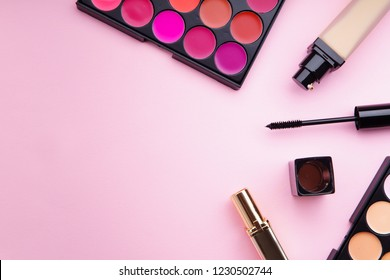 Top view picture of makeup products: lipstick and concealer palettes, foundation, mascara and eyelash curler on pink background. Feminine accessories concept