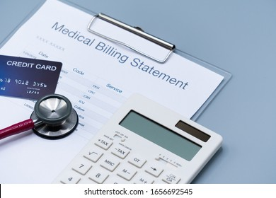 top view picture of medical billing statement, cradit card, white calculator and pink stethoscope on the gray background. health record, insurance and healthcare concept