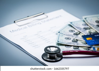 top view picture of medical billing statement, cradit card,  banknotes and pink stethoscope on the gray background