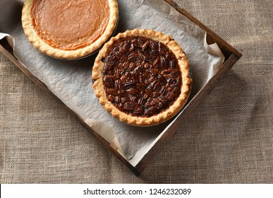 Top view of a piecan pie and pumpkin pie in a wood box on a burlap table cloth.