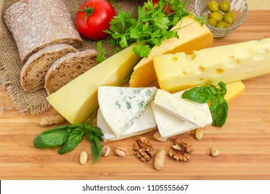 Top view of pieces of different soft, semi-soft, medium-hard and hard cheese among of brown bread, nuts, vegetables and greens on the bamboo wooden surface