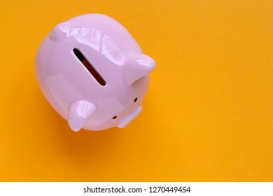 top view of piggy bank isolated on yellow background