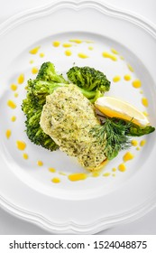 Top view of pike perch or zander fillet in cream sauce with broccoli isolated. Restaurant main course with fried sander fish or pike meat with lemon and greens topview