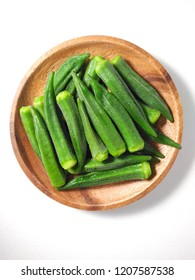 Top view of pile of fresh green okra on wooden plate isolated on white background. Healthy vegetable and plant. Common cooking ingredients in Taiwan. With copy space.
