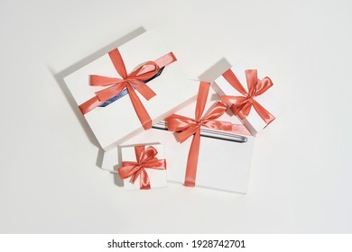 Top view of a pile of gift boxes of different sizes with red bows on white background. Birthday, holidays and celebration concept