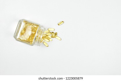 Top view of pile overflow of fish oil capsules in a glass bottle on white background. Omega 3. Vitamin E. Supplementary food background.
