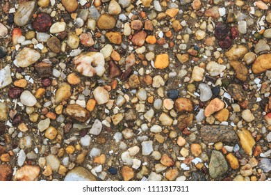 Top view of pile of pebbles of various colours forming textured background. Texture made with elements of nature to raise awareness about the environment.