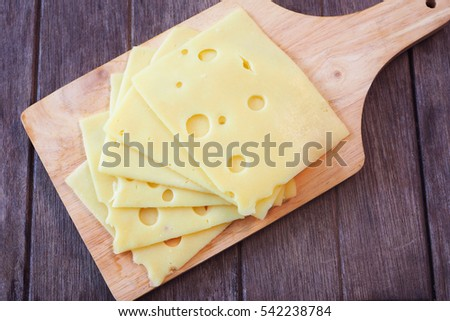 Top view of pile of swiss cheese slices on a wooden table.