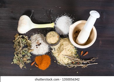 top view of piles of Seasoned Salts with ingredients and mortar on dark brown wooden table