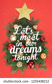 """top view of pine tree branches, golden star and christmas balls arranged in christmas tree isolated on red with """"lets meet in our dreams tonight"""" inspiration"""