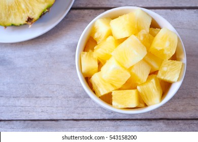 Top view of pineapple chucks in a bowl on a wooden table.