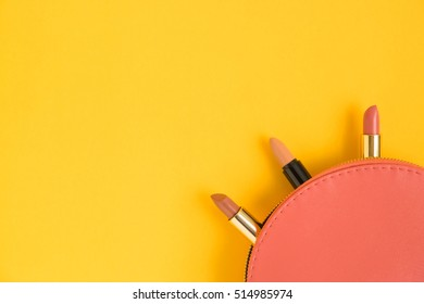 Top view of pink cosmetic bag consist of three lipsticks on yellow background