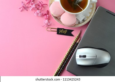 Top view of pink hyacinth, laptop, tea cup, cell phone and French macarons on pink background. Feminine workspace desktop with copy space.