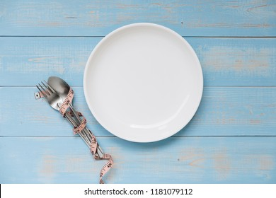 Top view Pink Measuring tape wrapped around fork and spoon with white dish on blue pastel color wooden table. dieting, weight loss and clean food concept