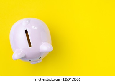 Top view of pink piggy bank on yellow background with copy space as debt or financial problem solution, saving money, finance calculate tax, investment, budget cost and expense.