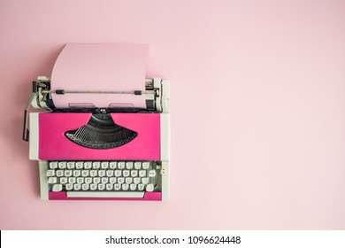 Top view of pink vintage typewriter with blank paper sheet on table. Space for copy.