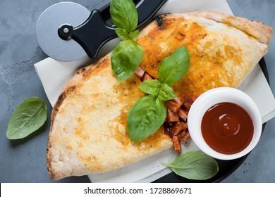 Top-Ansicht von Pizzakalzone mit Prosciutto- und Mozzarella-Käse, horizontal auf grauem Beton geschossen