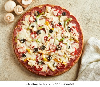 Top view of pizza with mushrooms, pepper, tomato and pepperoni