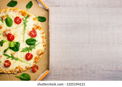 top view of pizza with tomatoes and herbs in cardboard delivery box and copy space over wooden table background