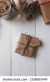 Top view of a plain brown paper wrapped Christmas present tied with twine on a white wood table. Vertical format with copy space at the bottom and wrapping supplies at the top.