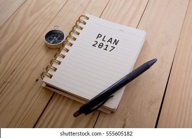 Top view of PLAN 2017 written on the notebook,travel planning concept.note book,compass,passport,film camera on the wooden desk.