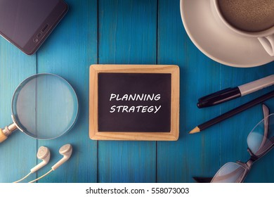 Top view of PLANNING STRATEGY written on the chalkboard,business concept.chalkboard,smart phone,cup,magnifier glass,glasses pen on wooden desk.