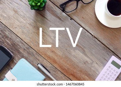 Top view of plant, sunglasses, a cup of coffee, calculator, pen, notebook,and mobile phone on wooden background written with LTV. Life time value.