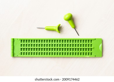 top view of plastic braille writing slate and stylus on brown table
