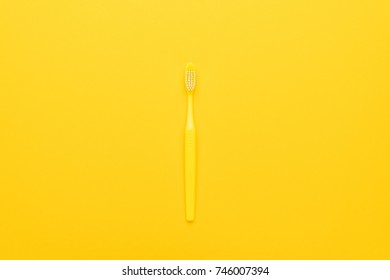 top view of plastic toothbrush on the yellow background