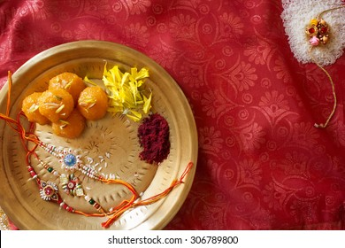 Top View of a plate containing Rakhi and ladoo with sindoor and some flowers marking the religious celebration of Raksha Bhandan.