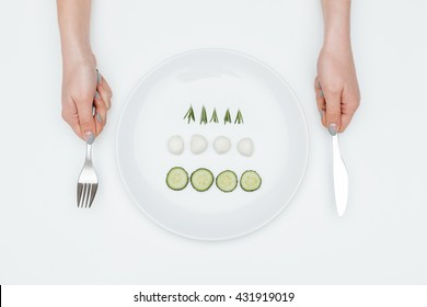 Top view of plate with cucumber, mozzarella and herbs and hands holding fork and knife over white background