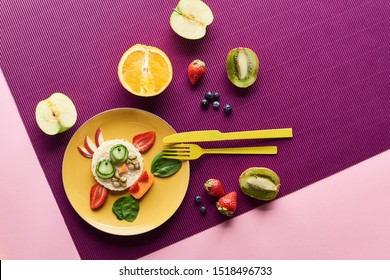 top view of plate with fancy cow made of food near fruits on purple background