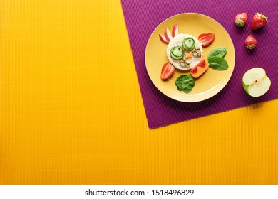 top view of plate with fancy cow made of food on purple and orange background