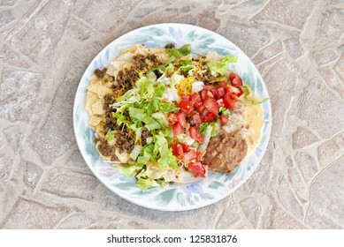 A top view of a plate filled with Mexican beef taco salad topped with lettuce, tomato, onion and cheese, horizontal with copy space