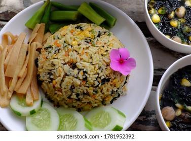 assiette de vue de dessus de plat de riz frit avec des légumes sous forme de concombre, tournage en bambou, soupe d'okra et d'algues pour le repas en famille au déjeuner, délicieuse nourriture végétalienne prête à manger sur fond bois